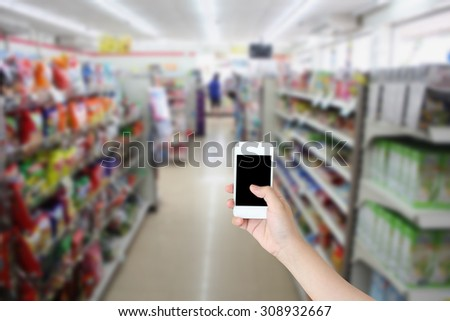 hand holding smartphone with convenience store shelves blurred background - stock photo