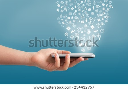 Hand holding smartphone with icons on a blue background - stock photo