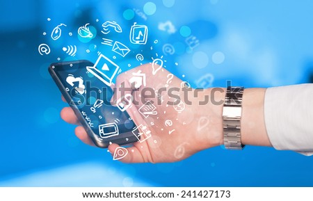 Hand holding smartphone with media icons and symbol collection - stock photo