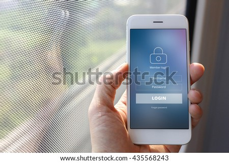 Hand holding smartphone with member loging screen on train window background - stock photo