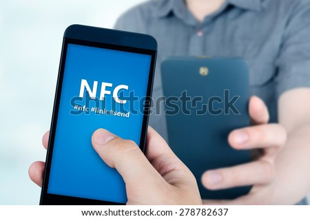 Hand holding smartphone with NFC technology - near field communication data transfer method - stock photo