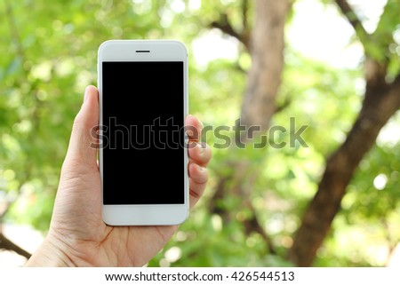Hand holding smartphone with organic background - stock photo
