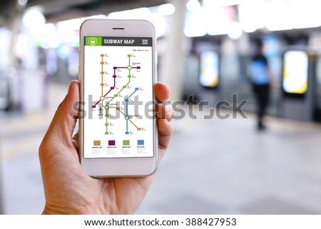 Hand holding smartphone with subway map application background - stock photo