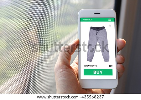 Hand holding smartphone with sweatpants ecommerce screen website - stock photo