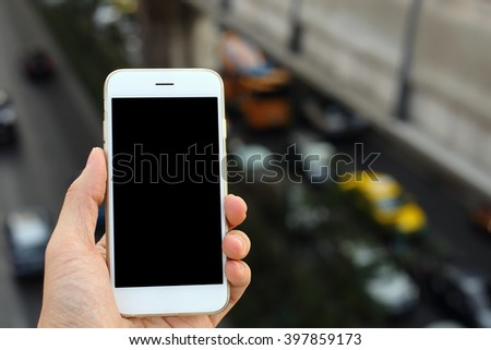Hand holding smartphone with traffic jam background - stock photo