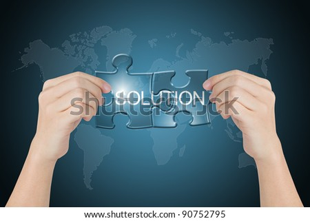 hand holding solution connected jigsaw puzzle with world map background - stock photo