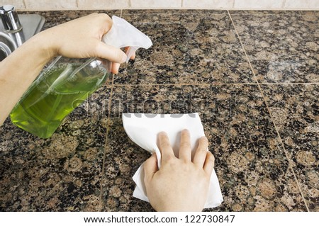 Hand holding spray bottle to clean stone kitchen countertops - stock photo