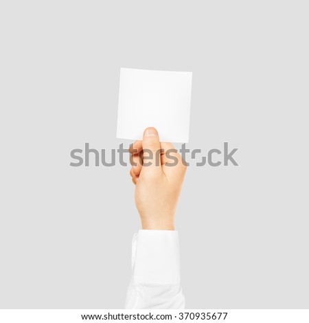 Hand holding square blank white sticker mock up isolated on gray. Stickering mockup holder. Empty paper clue remnder hold in hands. - stock photo