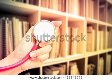 hand holding stethoscope with blur perspective bookshelf and day light - stock photo