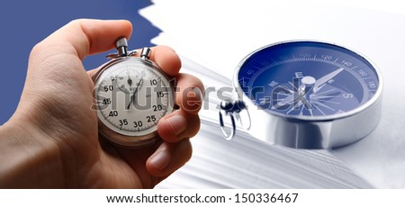 Hand holding stopwatch, stack of paper cards and compass - stock photo