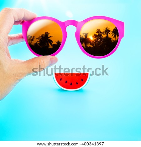 hand holding summer pink sunglasses with palm tree view and watermelon at light blue background,Summer Holiday,Leave space for adding your text - stock photo