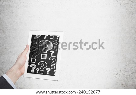 Hand holding Tablet Computer with question mark - stock photo