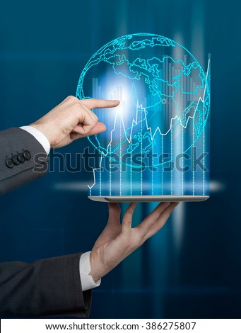 Hand holding tablet, hand touching hologram picture of Earth over it. Concept of international business. - stock photo
