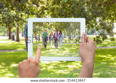 Hand holding tablet pc against froup of college students walking in the park - stock photo