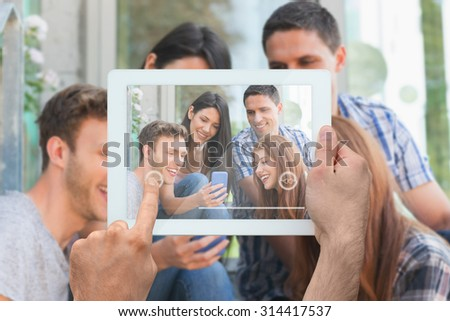 Hand holding tablet pc against happy students looking at smartphone outside on campus - stock photo