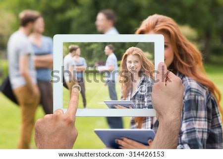 Hand holding tablet pc against pretty student studying outside on campus - stock photo