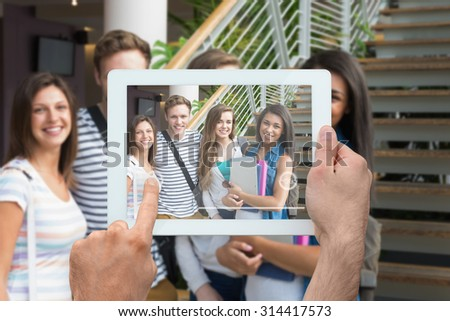 Hand holding tablet pc against smiling students looking at camera outside - stock photo