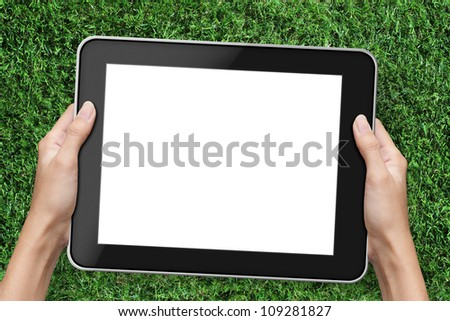 Hand holding tablet pc. over green grass background. - stock photo