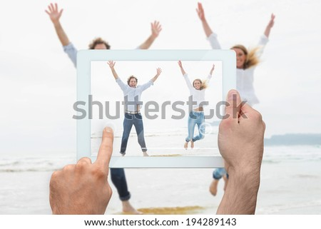 Hand holding tablet pc showing cheerful young couple jumping at beach - stock photo