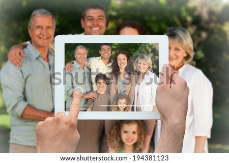 Hand holding tablet pc showing family looking at the camera in the park - stock photo
