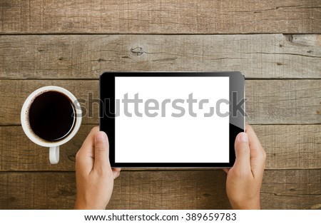 hand holding tablet similar to ipades style on wood table - stock photo