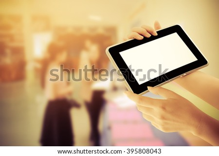 hand holding tablet with blur people in booth showcases  background - stock photo