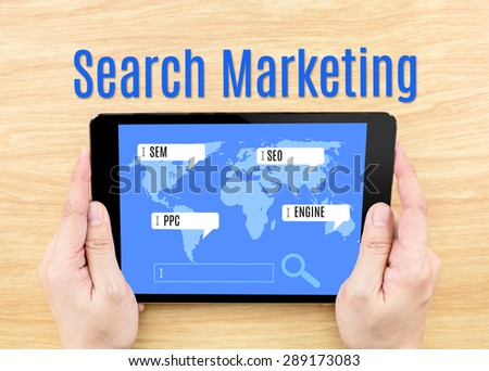 Hand holding tablet with Search Marketing word on wooden table,digital business concept - stock photo