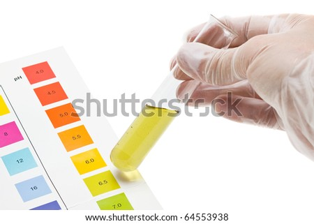 Hand holding test tube with pH indicator comparing color to scale - stock photo