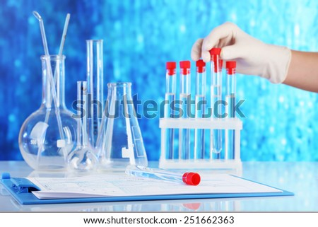 Hand holding test tubes and clipboard with medical history form on table on blue background - stock photo