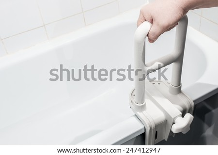 hand holding the handrail in the bathroom. Focus on the handrail. - stock photo