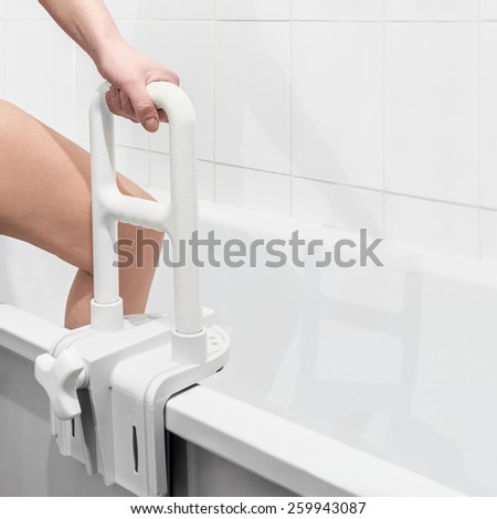 hand holding the handrail in the bathroom. Focus on the handrail. empty space can be used for the text - stock photo