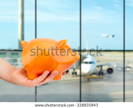 hand holding the piggy bank at the lounge airport - stock photo