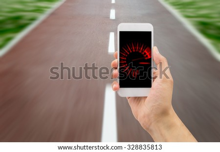 hand holding the smartphone with tachometer speed in the screen over the road in background - stock photo
