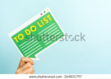 """Hand holding """"To-do list"""" green message to the left and blank space to the right. Blue background. - stock photo"""
