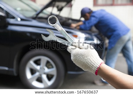 hand holding tools and car service concept - stock photo