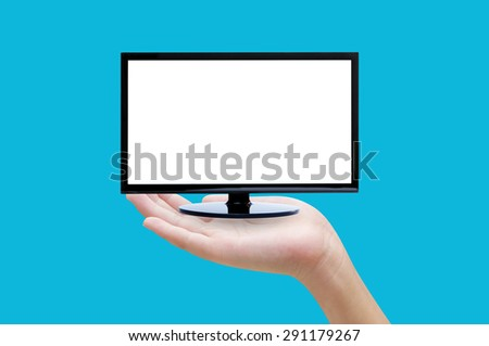 Hand holding tv on blue background - stock photo