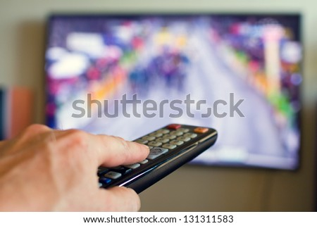 Hand holding TV remote control with a television in the background. - stock photo