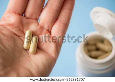 Hand holding two capsules and opened medicine bottle in the background - stock photo