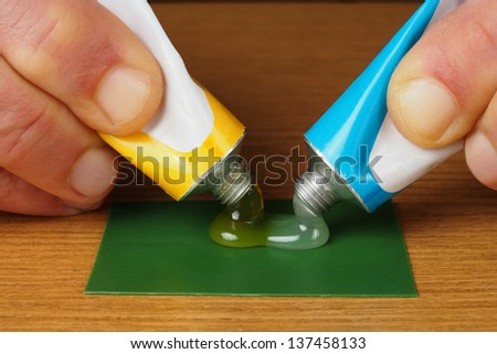 Hand holding two tubes with epoxy glue ingredients, resin and hardener - stock photo