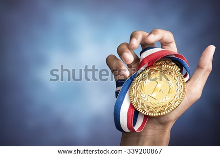 hand holding up a gold trophy cup as a winner in a competition - stock photo
