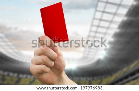 Hand holding up red card against football stadium - stock photo