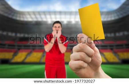 Hand holding up yellow card against stadium full of germany football fans with player - stock photo