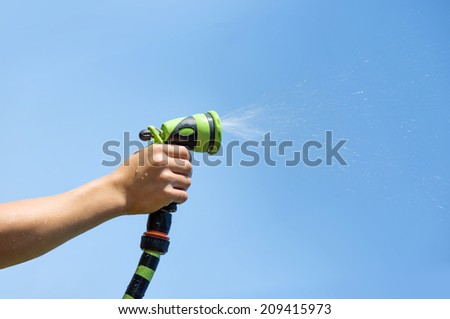 Hand holding water sprinkler against blue sky, irrigating - stock photo