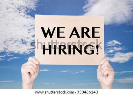 hand holding we are hiring! sign on blue sky background  - stock photo
