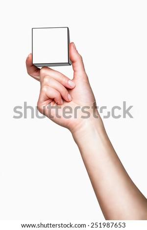 Hand holding white cube on white background - stock photo