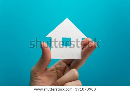 Hand holding white paper house figure on blue background. Real Estate Concept. Ecological building. Copy space top view. - stock photo