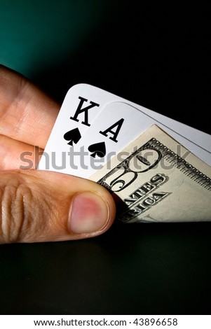 Hand holding winning cards and banknote - stock photo