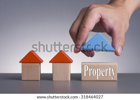Hand holding wooden house (Housing Loan Concept) with word Property - stock photo