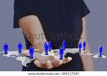 Hand holding world map with people - stock photo