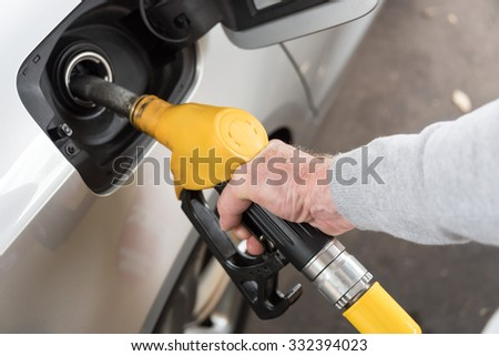 Hand holding yellow fuel pump nozzle and refilling car - stock photo